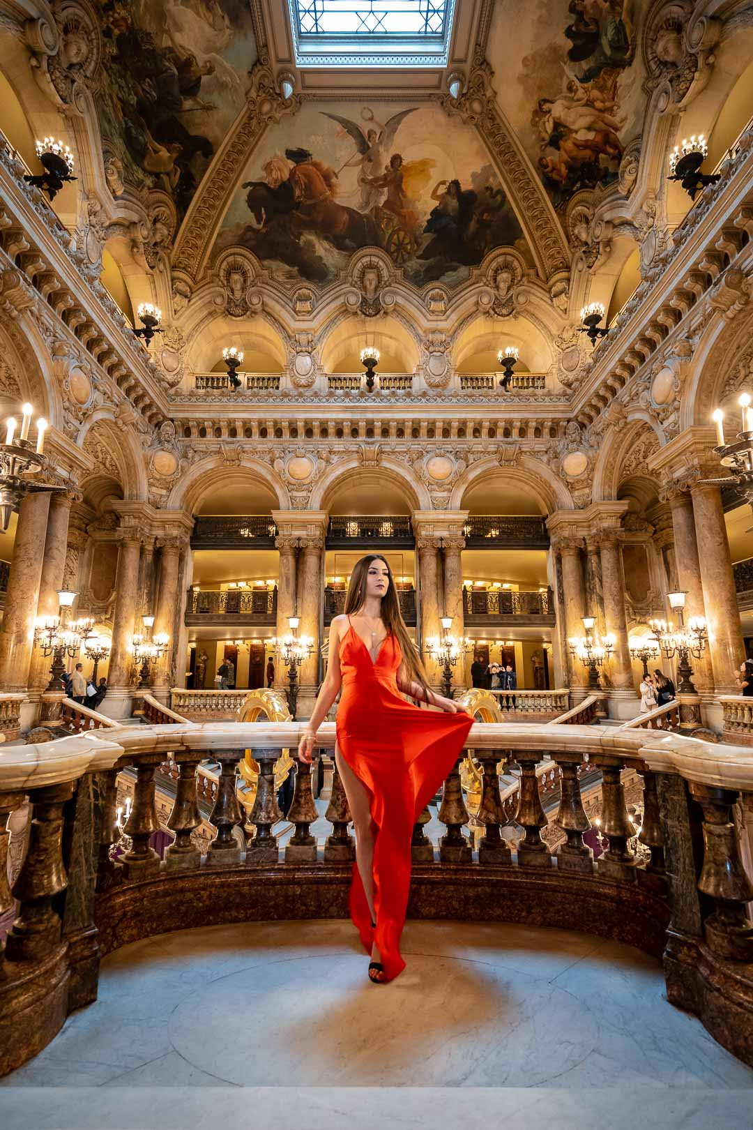 Woman in a red dress on a balcony of the grand hall of the Opéra Garnier