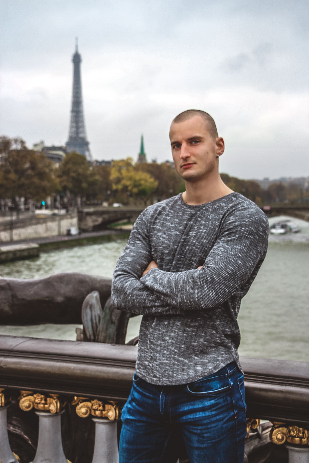 Muscular man with a gray top poses in front of the Eiffel tower