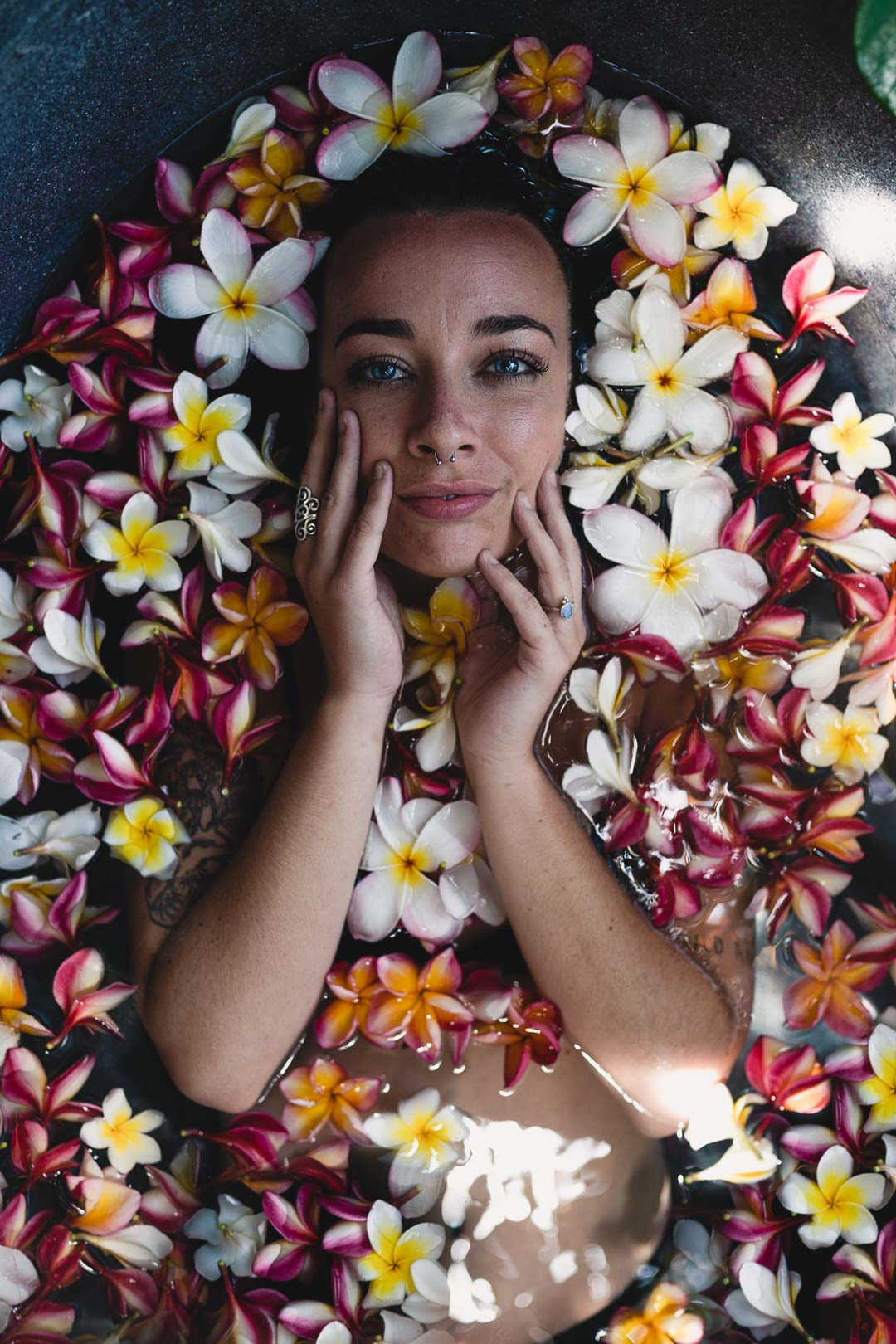Woman model in a bathtub filled with colorful Balinese flowers