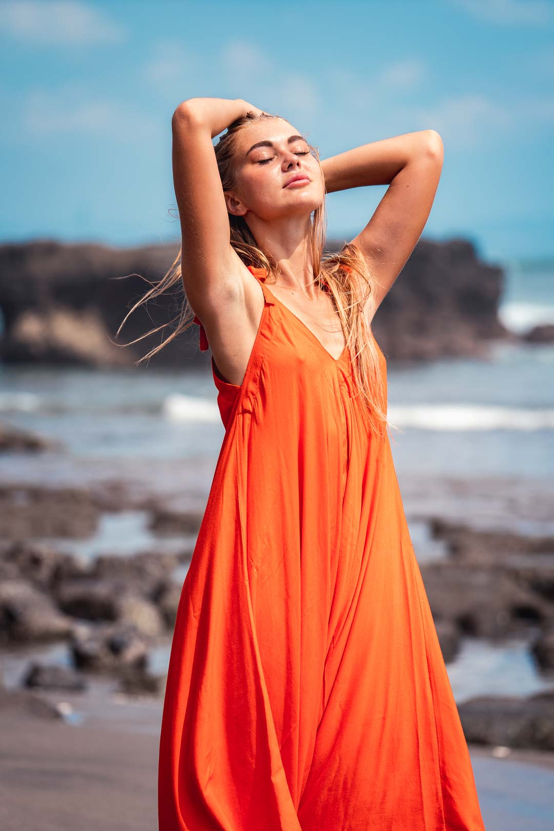 Photograph of a blonde model in an orange dress on a beach