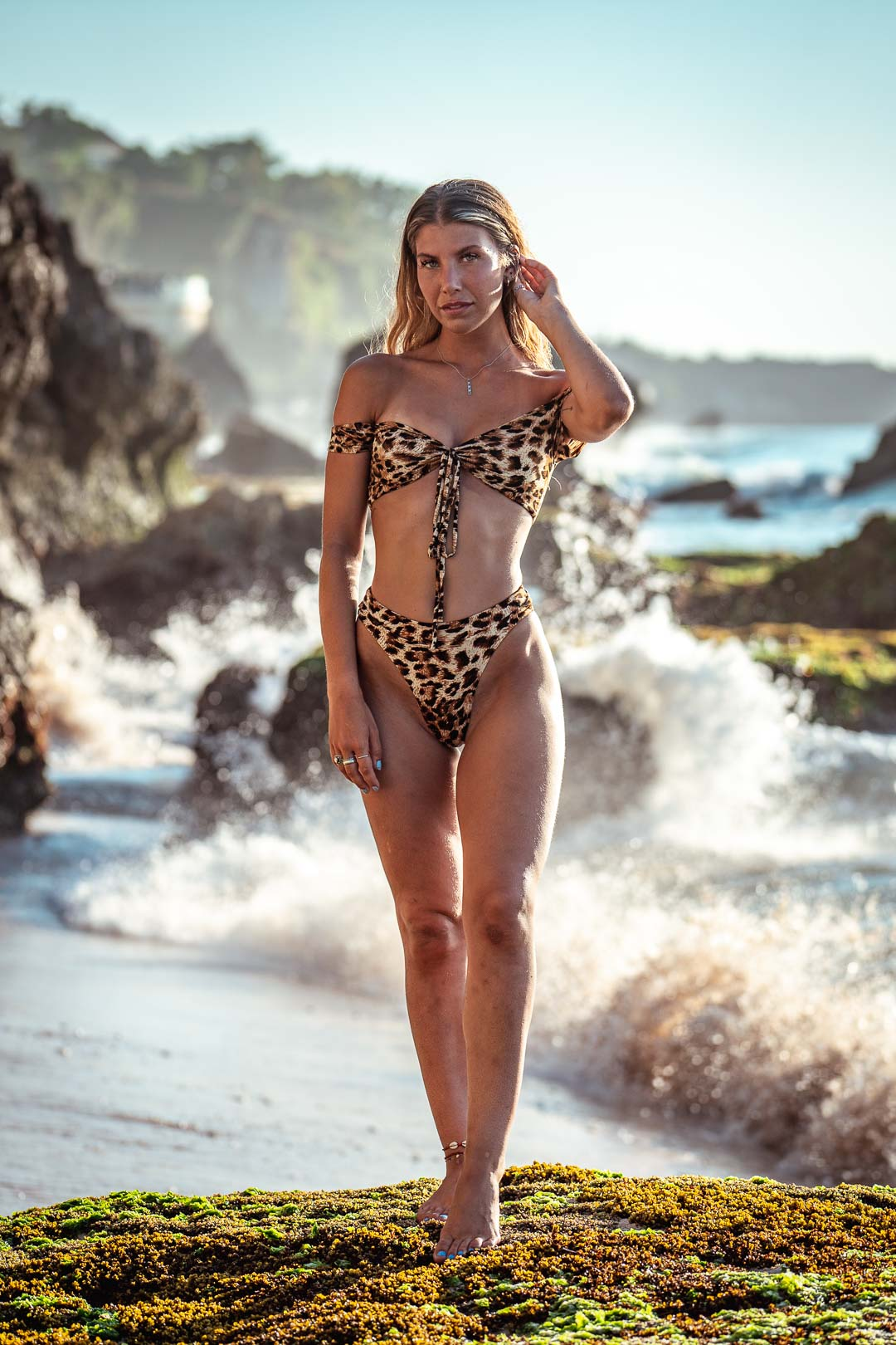 Woman in swimsuit with panther pattern in front of the powerful waves of Uluwatu beach