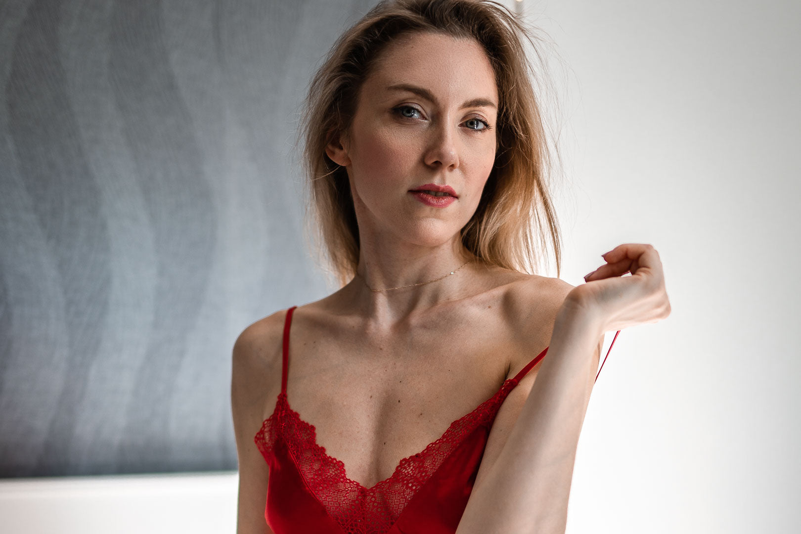 Woman model in red satin lingerie posing in a room