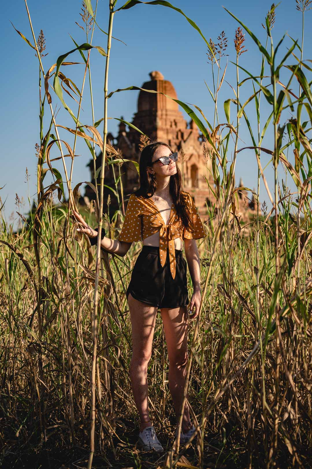 Woman model in a rice field in front of a Bagan temple