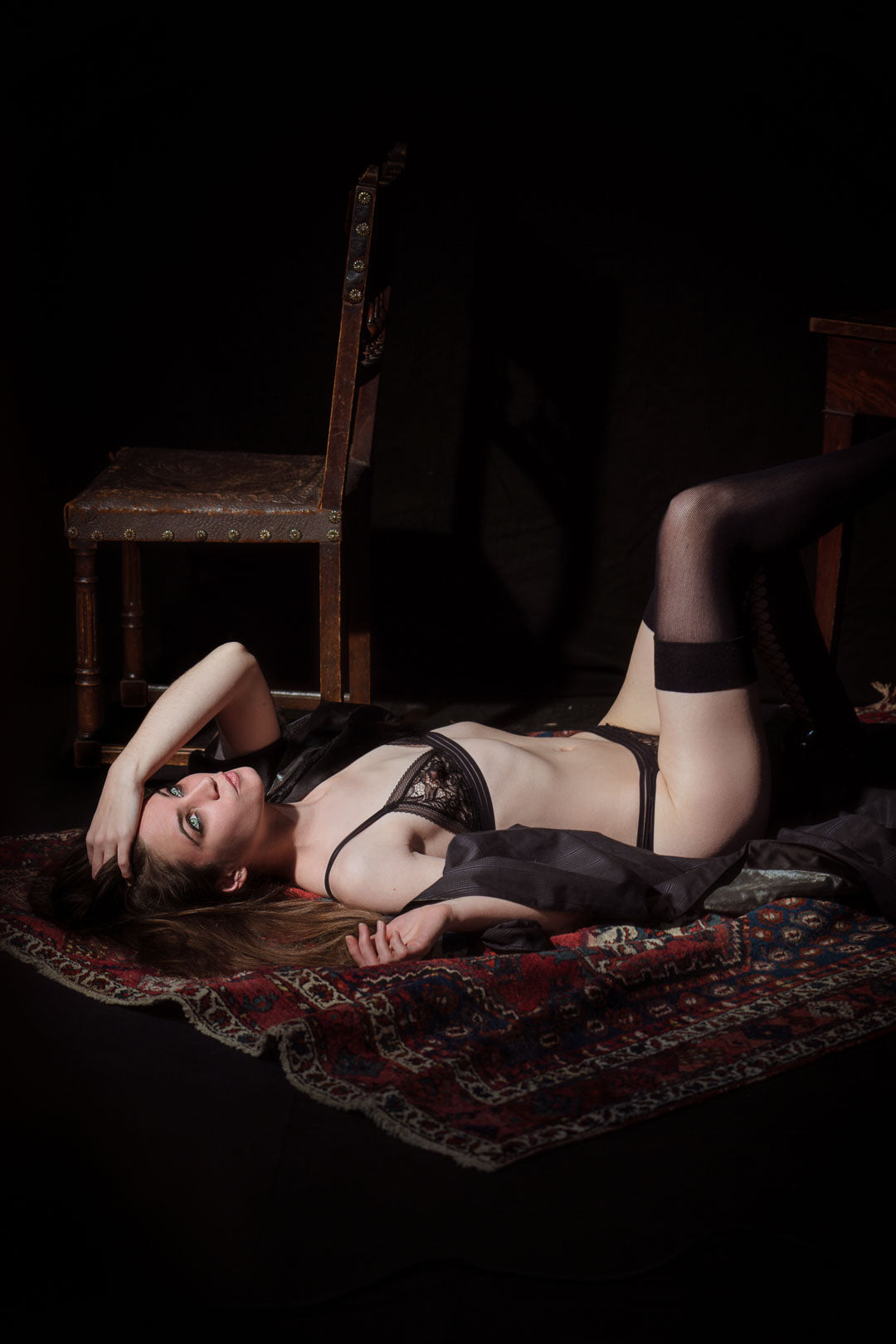Woman in black lingerie lying on a carpet in a boudoir atmosphere