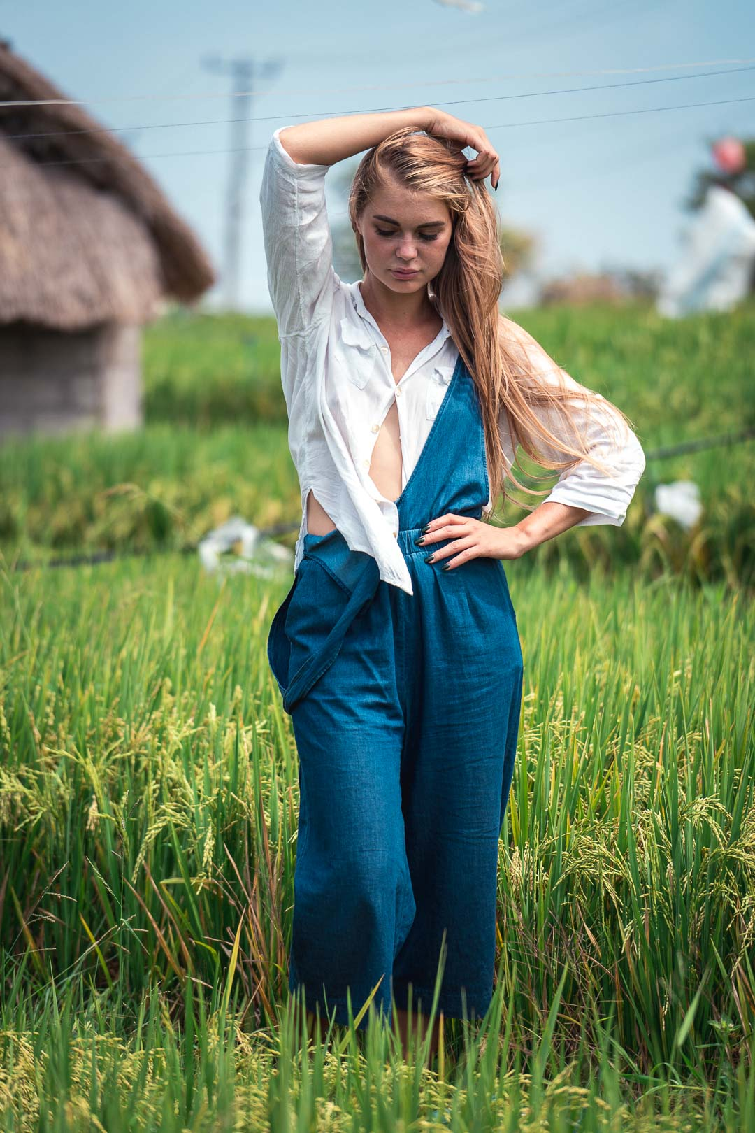 Blond woman in blue overalls standing in a rice field
