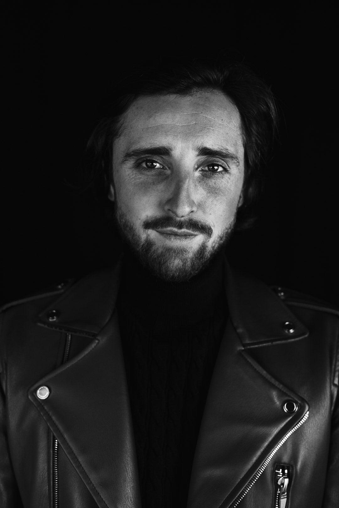 Black and white portrait of a man wearing a leather jacket