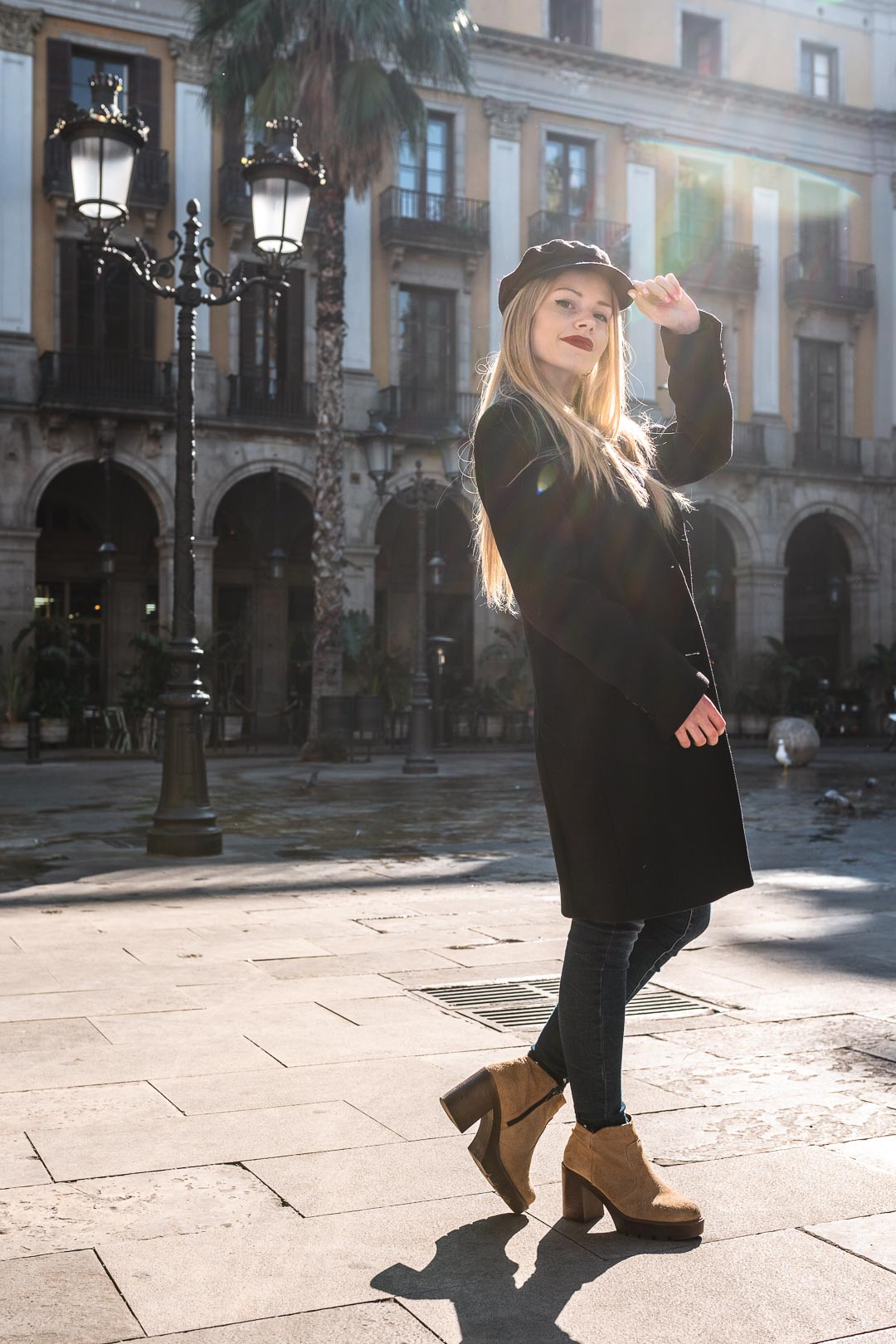 Blond woman in black clothes lit by a ray of sunshine