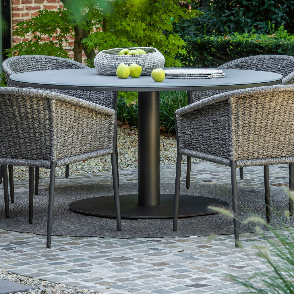 round dining table with grey glass top and grey pedestal base