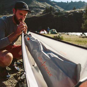 man inflating an Oru float bag