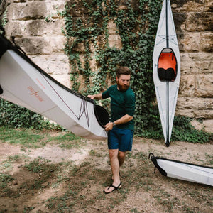 man carrying an Oru Kayak Bay ST down to the river