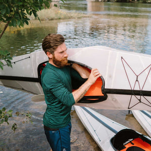 man carrying an Oru Kayak Bay ST up from river