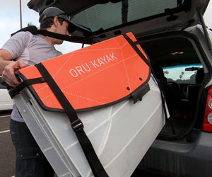 man putting Oru Kayak Coast XT into back of car