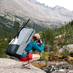 man wearing Oru Kayak backpack taking photo of mountain
