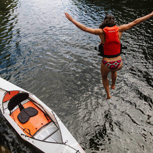 woman jumping into water with Oru Kayak Beach LT