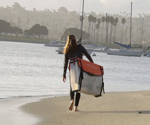 woman walking on beach carrying Oru Kayak Coast XT