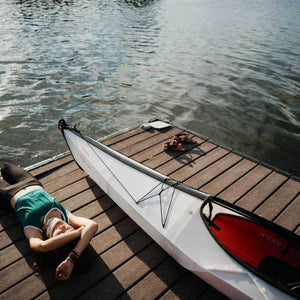 woman relaxing on wharf with an Oru Kayak Bay ST
