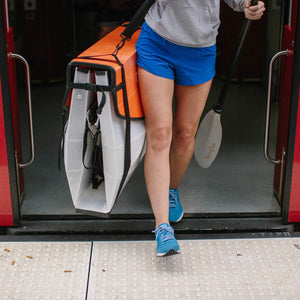 woman exiting train carrying an Oru Kayak Bay ST folded box
