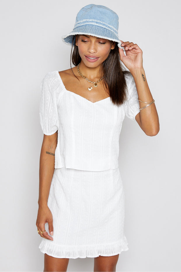 A fresh twist on a classic white top. Features a dot-textured fabric, puffed sleeves, and ruching at the back to create the perfect, flattering fit. Pair with your favorite classic denim, or a monochromatic white on white look!  100% Cotton