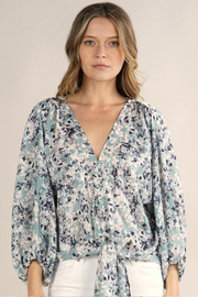 Every detail of this top contributes to how flattering it looks! The v-neck style with the front tie and relaxed sleeves lays beautifully on. The obscure floral print add a unique touch. 100% POLYESTER