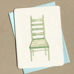 Outside of dirty greeting cards shows watercolor of a green chair.