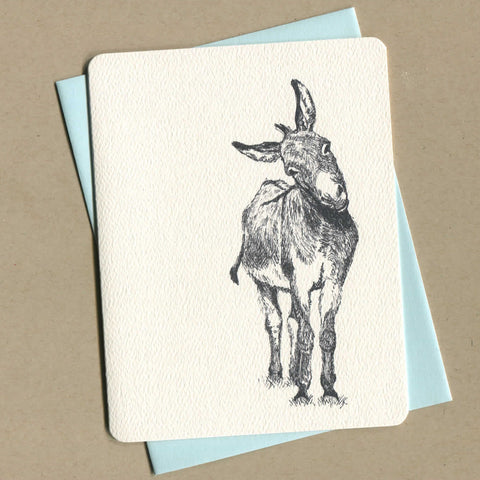 Outside of dirty greeting card shows a black and white illustration of a donkey.