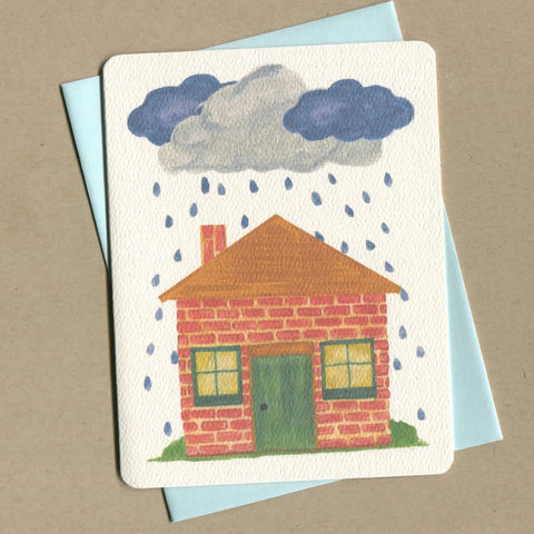 Outside of dirty greeting card shows watercolor of a house on a rainy day.