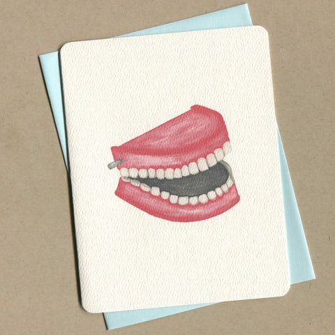 Outside of dirty greeting card shows watercolor of a set of chattering teeth toy.