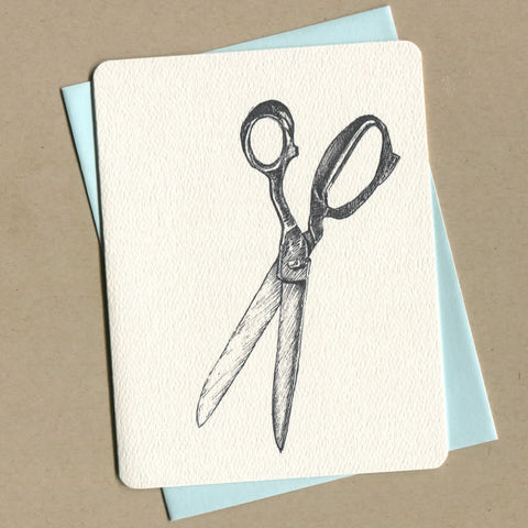 Outside of dirty greeting card shows black and white illustration of scissors.