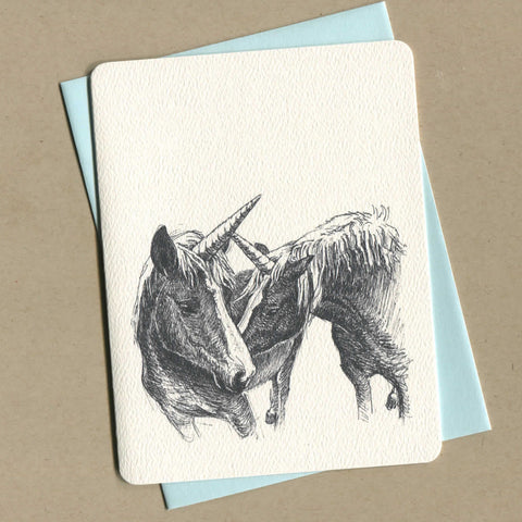Outside of dirty greeting cards shows illustration of two unicorns.