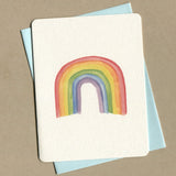 Outside of queer greeting card shows a watercolor of a rainbow.