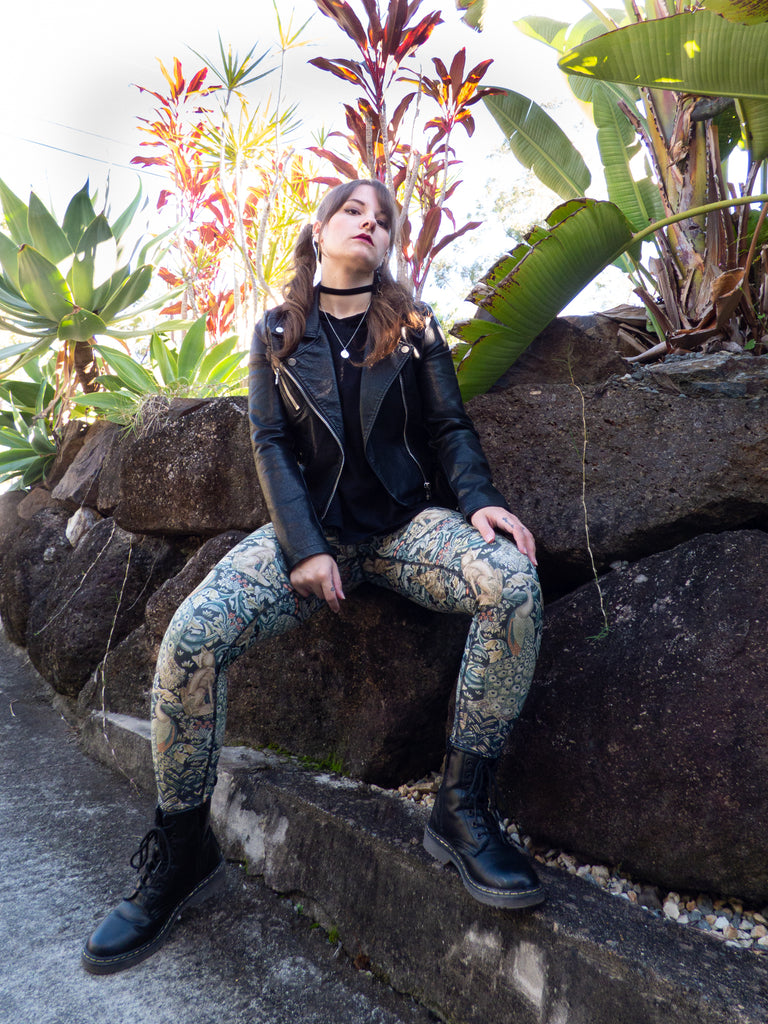 Woman sitting on rocks with leather jacket and Idyll Legging