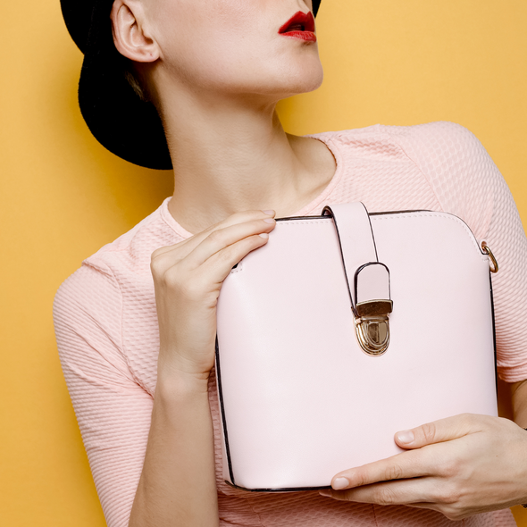 lady-holding-pink-handbag-with-pink-jumper-and-yellow-background