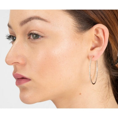 woman wearing cubic zirconia and rhodium plated silver large  hoop earrings with free gift pouch