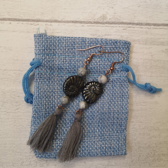 Grey vintage fossil shell and tassel statement earrings on blue hessian bag