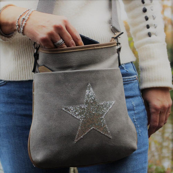 Grey cross body handbag with silver star on front