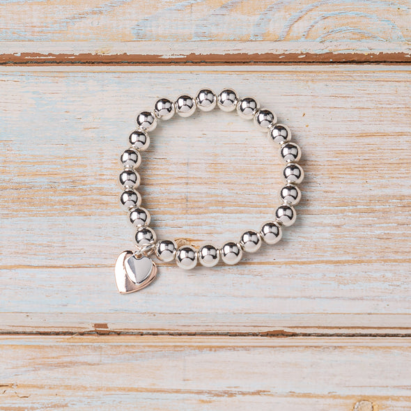 silver ball bracelet with rose gold and silver heart charm on wooden board