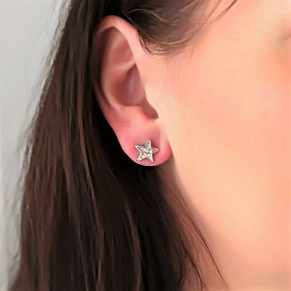 silver star stud earring on model with brown hair