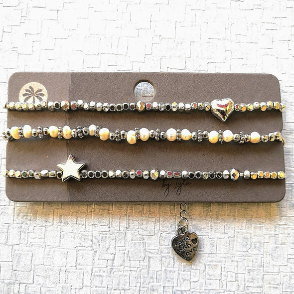 Three silver and pearl bracelets with star and heart on card