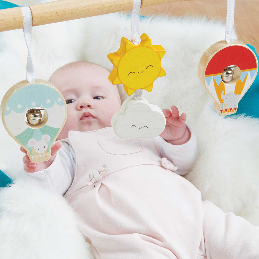 Baby girl playing with baby gym rainbow cloud hot air balloon theme made of solid sustainable wood