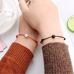 Holding hands with string bracelets with natural stone charms