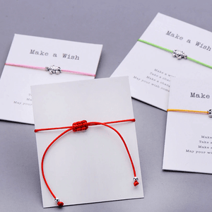 back of the gift card with a red string bracelet on