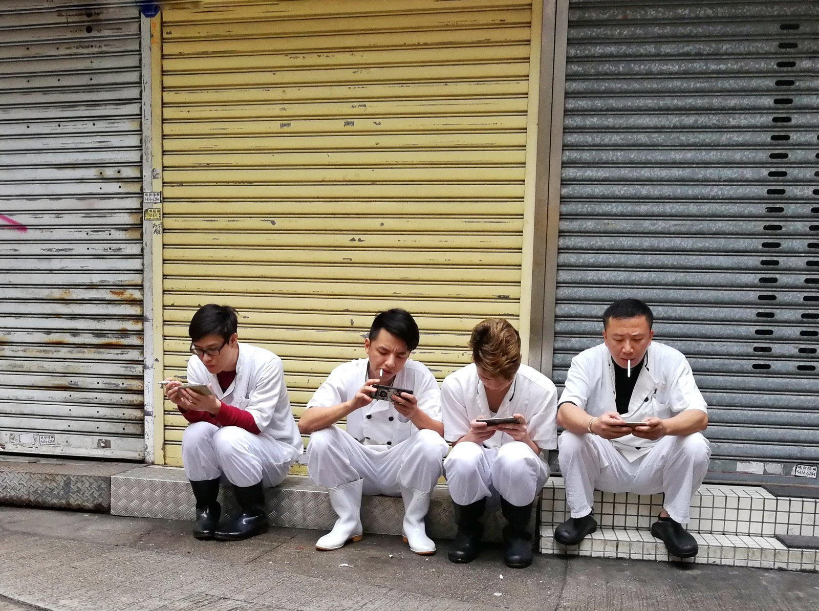 A group of people sitting on a bench watching their phone