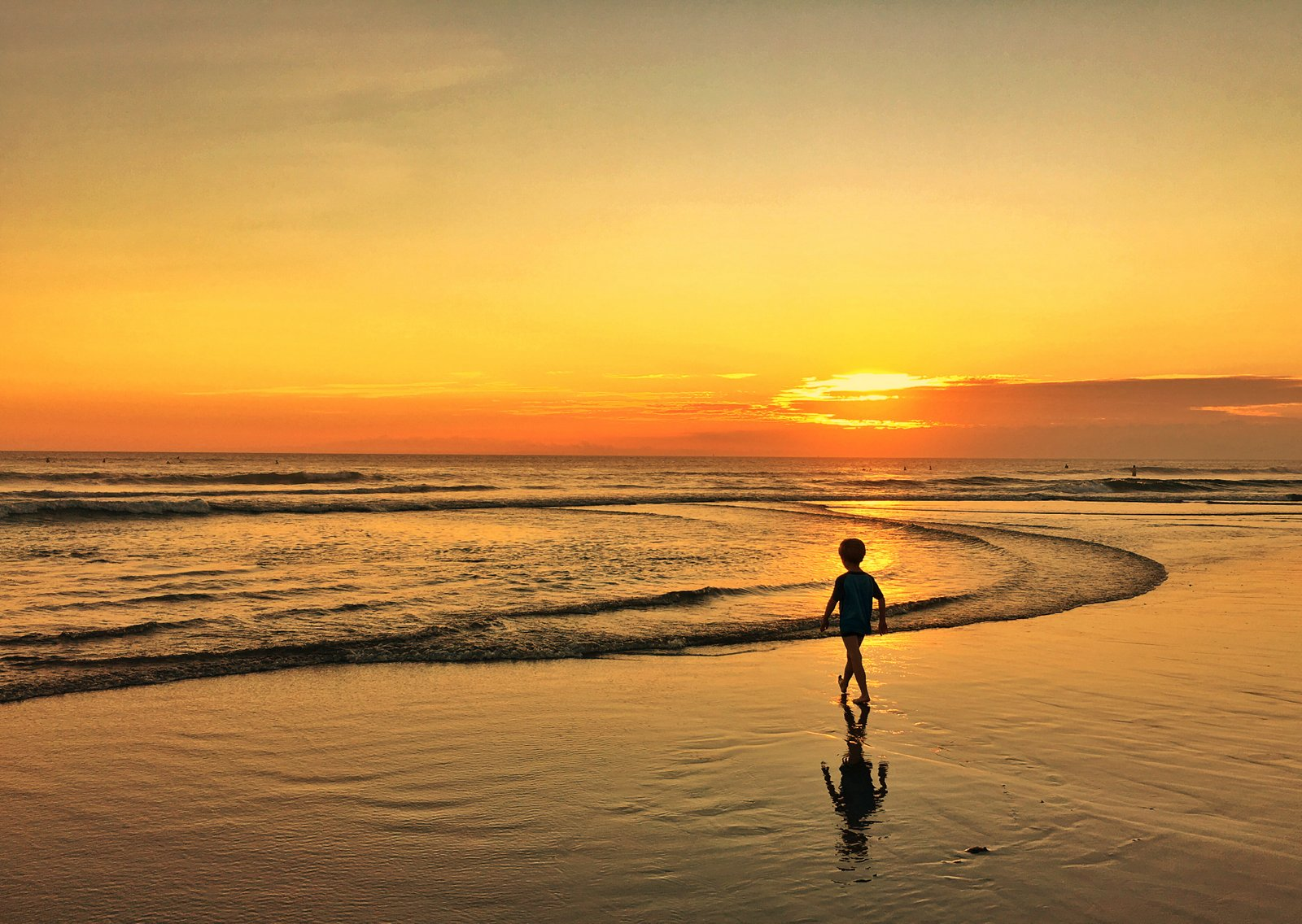 A kid standing on a beach with a sunset in the background