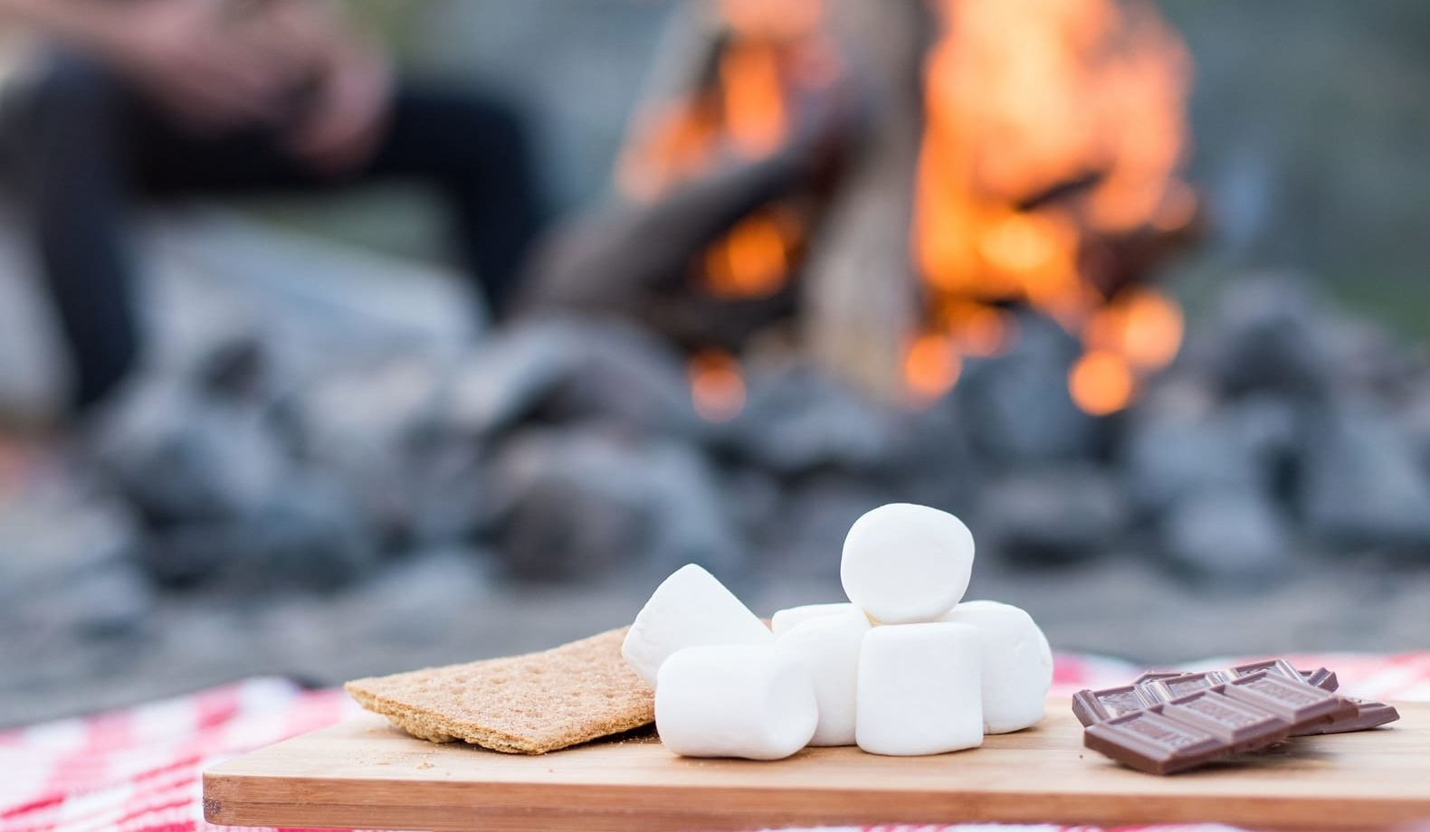 Chopping board with marshmallows, chocolate and biscuit in front of a camp fire