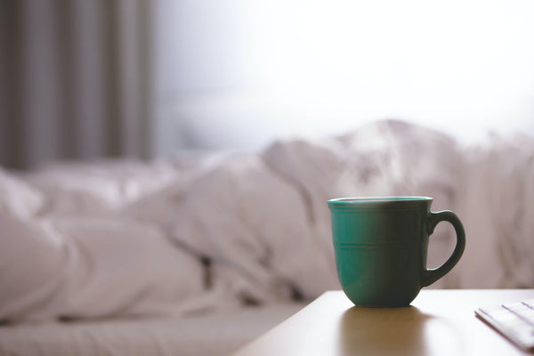 A cup of hot tea or herbs next to a bed, Natural Sleep Remedy header image