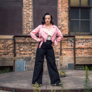Pinup Model Pamela Marie is wearing a Lana Biker Jacket in pink, 1950's White & Black Polka Dot Off Shoulder Ruffle Frenchie Top, and Kiki High Waisted Jeans.