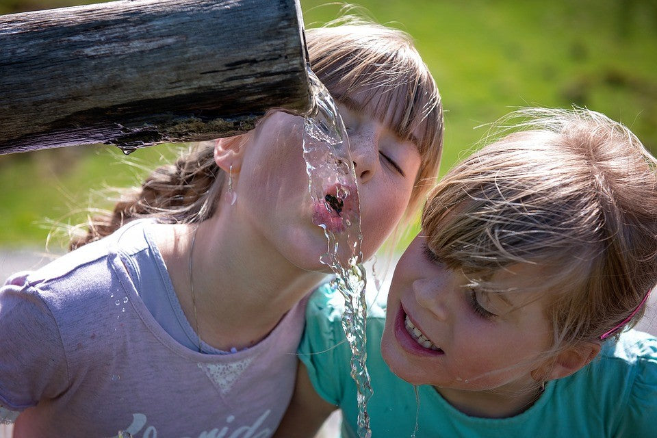 two little girls are drinking water