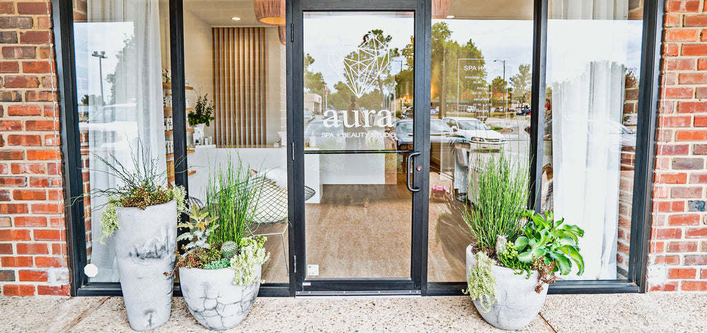Entrance to Aura Spa + Beauty Studio in Norman, Oklahoma surrounded by succulents and marble planters.