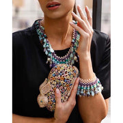 Woman Wearing Aquamarine And Amethyst Necklace With Matching Bracelet And Holding Multicoloured Bunny Clutch Bag