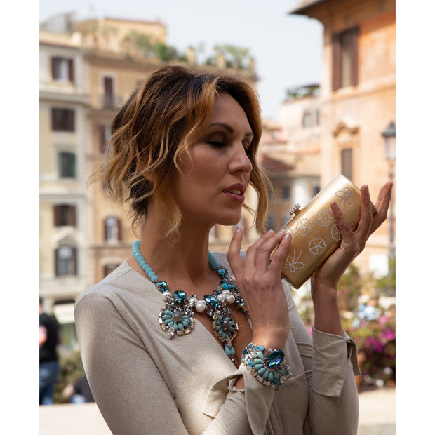Woman Wearing Pear & Emerald Cut Aquamarine Crystals And Turquoise Necklace & Holding Gold Clutch
